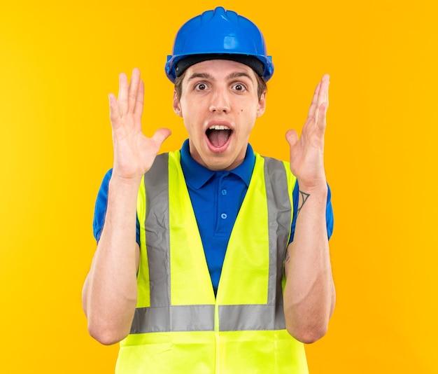 Zaskoczony młody budowniczy mężczyzna w mundurze podnoszący ręce
