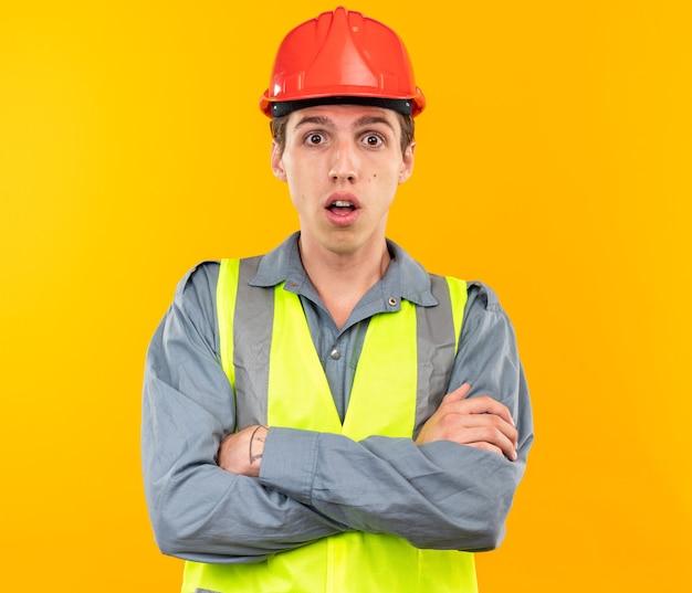 Zaskoczony młody budowniczy mężczyzna w mundurze skrzyżowanymi rękami