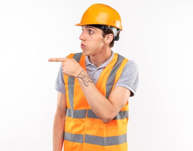 Zaskoczony młody budowniczy patrzący z boku w jednolitych punktach z boku