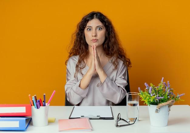 Zaskoczony, młody całkiem żeński pracownik biurowy siedzi przy biurku z narzędzi biurowych pokazując módl się gest na białym tle na pomarańczowo