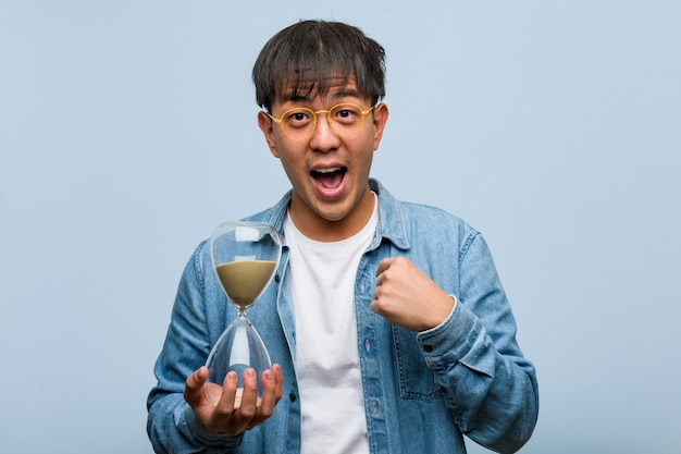 Zaskoczony młody chińczyk trzymający zegar piaskowy, czuje się dobrze i dostatnio