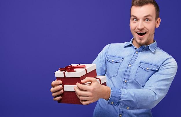 Zaskoczony młody chłopak stojący z dwoma prezentami w ręku.