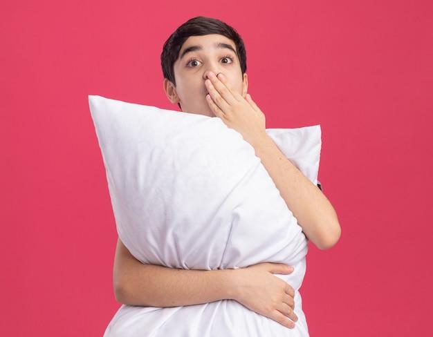 Zaskoczony młody chłopak trzymający poduszkę, kładący rękę na ustach, patrząc prosto na różową ścianę