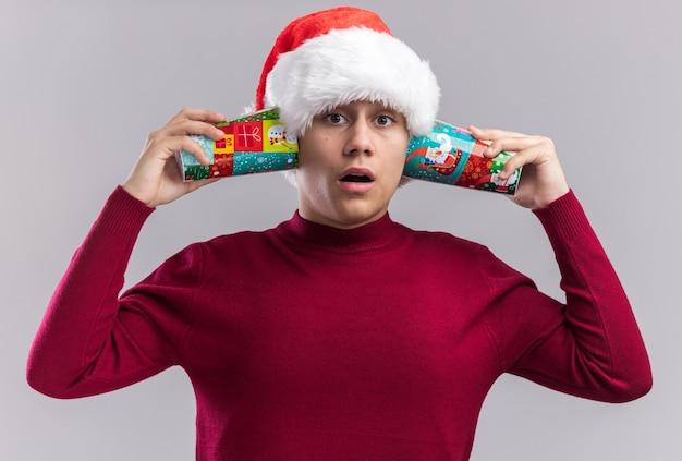 Zaskoczony, młody chłopak w kapeluszu boże narodzenie trzymając kubki świąteczne na uszach na białym tle
