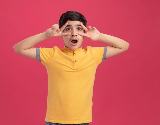 Zaskoczony młody chłopiec rasy kaukaskiej, patrzący prosto, pokazując symbole v w pobliżu oczu