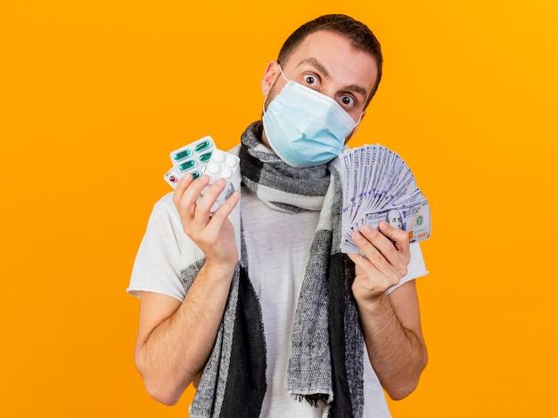Zaskoczony, młody chory człowiek ubrany w czapkę zimową i maskę medyczną, trzymając gotówkę z pigułkami na białym tle na żółtym tle