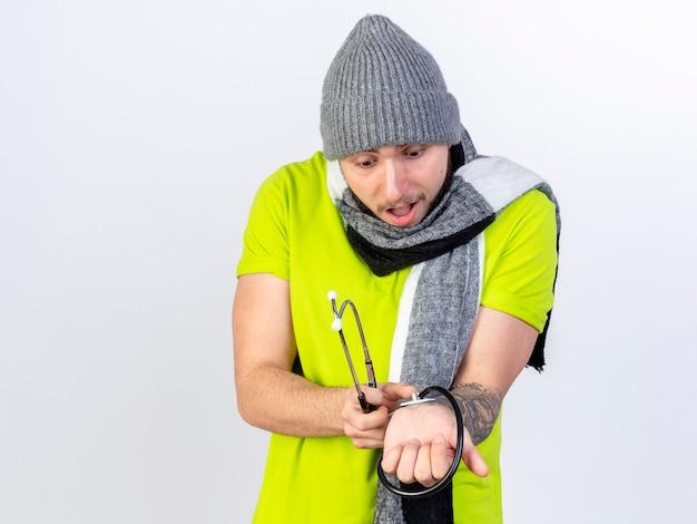 Zaskoczony, młody chory człowiek ubrany w czapkę zimową i szalik trzyma stetoskop pod ręką na białym tle na białej ścianie