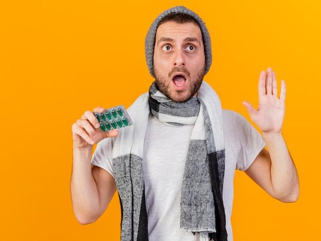 Zaskoczony, młody chory człowiek ubrany w czapkę zimową i szalik, trzymając pigułki i pokazując gest stop na białym tle na żółtym tle