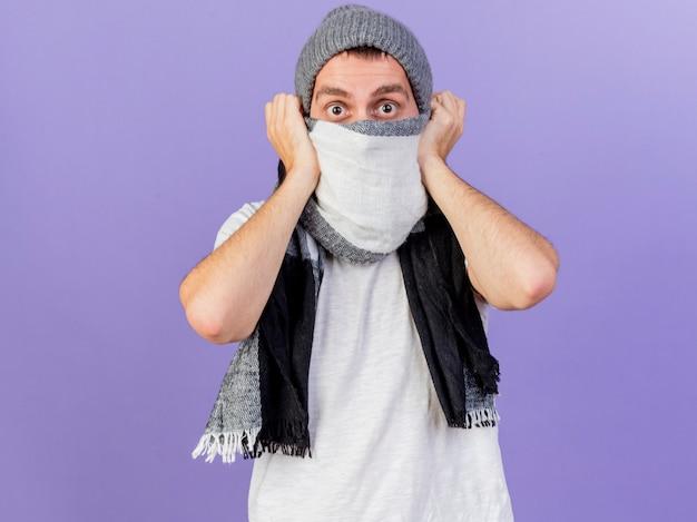 Zaskoczony, młody chory człowiek w czapce zimowej z szalikiem zakrytym twarzą z szalikiem na białym tle na fioletowym tle
