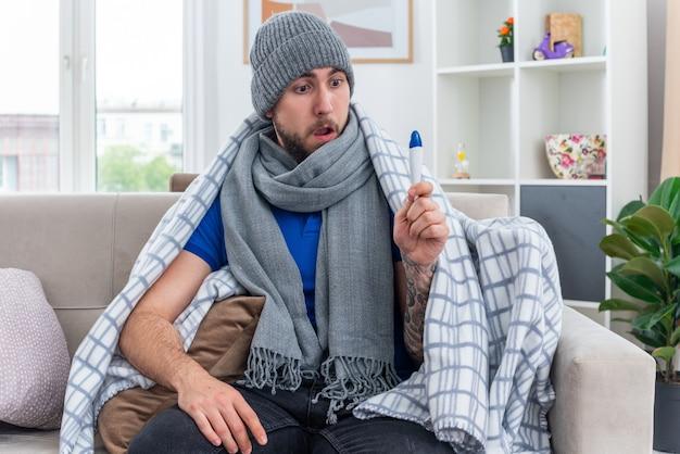 Zaskoczony młody chory mężczyzna ubrany w szalik i czapkę zimową owiniętą w koc, siedzący na kanapie w salonie, trzymając rękę na nodze i patrząc na termometr