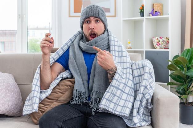 Zaskoczony młody chory mężczyzna ubrany w szalik i czapkę zimową zawiniętą w koc, siedzący na kanapie w salonie, trzymający się i wskazujący na termometr patrzący w przód