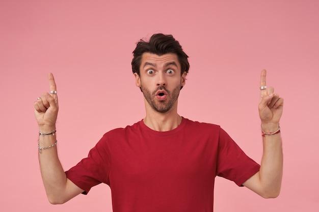 Zaskoczony, młody ciemnowłosy mężczyzna z brodą, stojący w czerwonej koszulce, patrząc zdziwiony i wskazujący w górę palcami wskazującymi, ściągający czoło i unoszący brwi