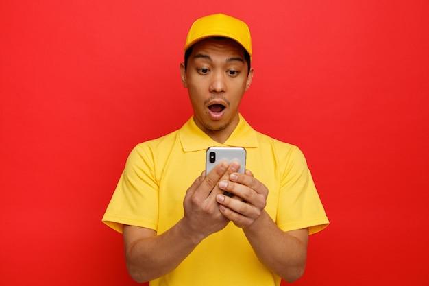 Zaskoczony młody człowiek dostawy czapkę i mundur trzymając i patrząc na telefon komórkowy