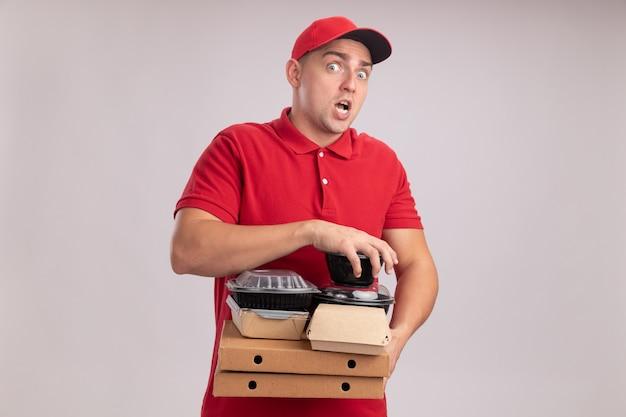 Zaskoczony młody człowiek dostawy ubrany w mundur z czapką, trzymając pojemniki na żywność na pudełkach po pizzy na białym tle na białej ścianie