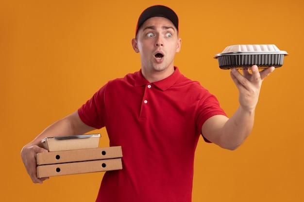 Zaskoczony młody człowiek dostawy ubrany w mundur z czapką, trzymając pudełka po pizzy i patrząc na pojemnik na żywność w ręku na białym tle na pomarańczowej ścianie