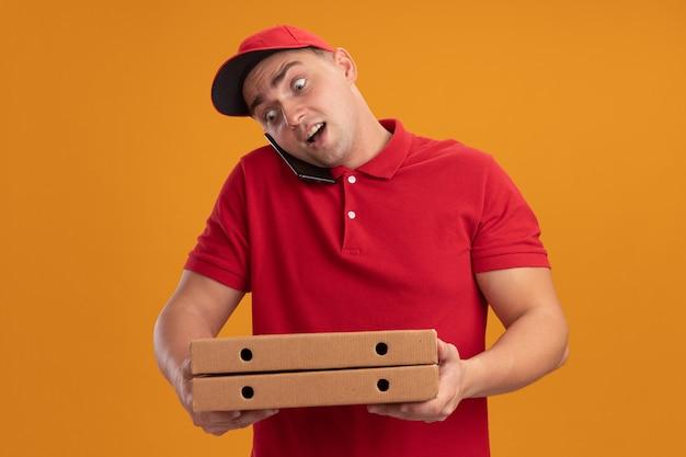 Zaskoczony młody człowiek dostawy ubrany w mundur z czapką, trzymając pudełka po pizzy, mówi przez telefon na białym tle na pomarańczowej ścianie