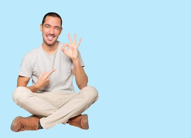 Zaskoczony młody człowiek gestem aprobaty