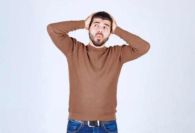 Zaskoczony młody człowiek o czarnych włosach trzymający ręce na głowie.