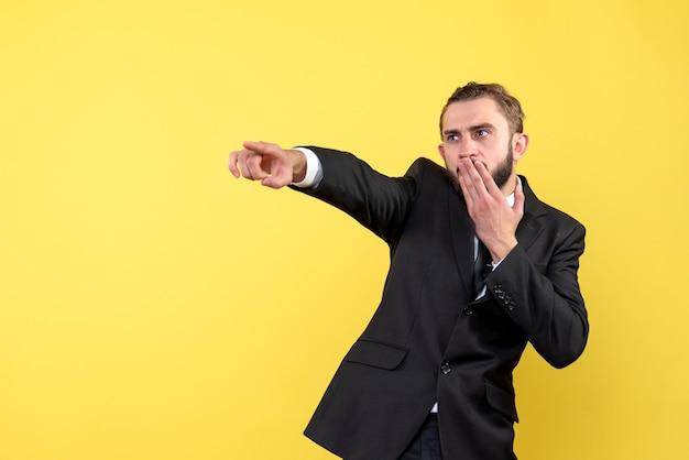 Zaskoczony młody człowiek pokazujący kierunek na żółto