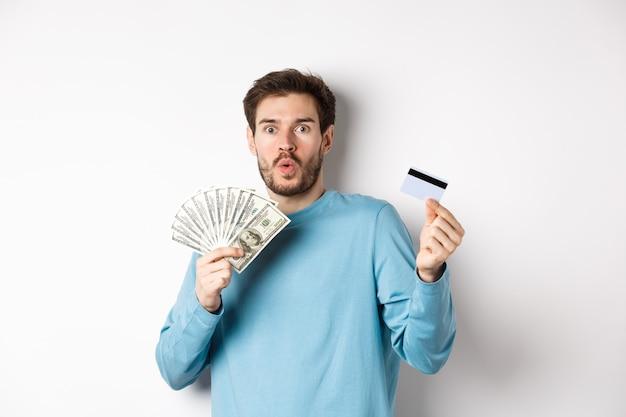 """Zaskoczony młody człowiek pokazujący pieniądze w dolarach i plastikową kartę kredytową, sapiąc i mówiąc """"wow"""" ze zdumioną miną, stojąc na białym tle."""