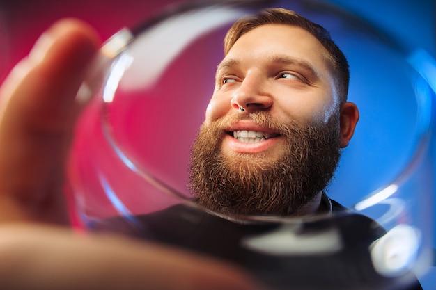 Zaskoczony młody człowiek pozuje przy lampce wina.