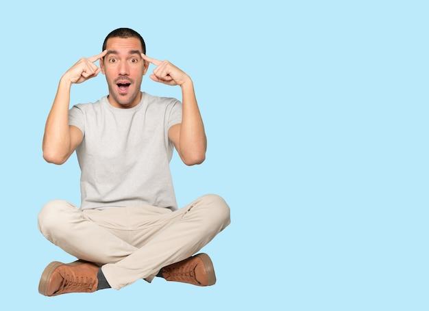 Zaskoczony młody człowiek robi gest koncentracji