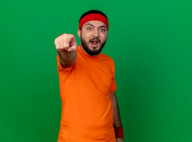 Zaskoczony, młody człowiek sportowy, noszenie opaski i opaski na rękę, pokazując gest na białym tle na zielonym tle z miejsca na kopię