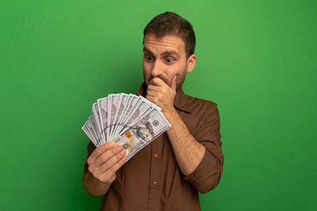 Zaskoczony, młody człowiek, trzymając i patrząc na pieniądze, trzymając rękę na ustach na białym tle na zielonej ścianie