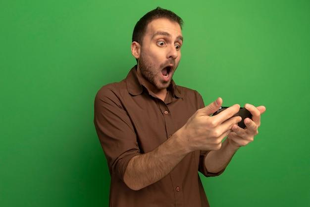 Zaskoczony, młody człowiek, trzymając i patrząc na telefon komórkowy na białym tle na zielonej ścianie