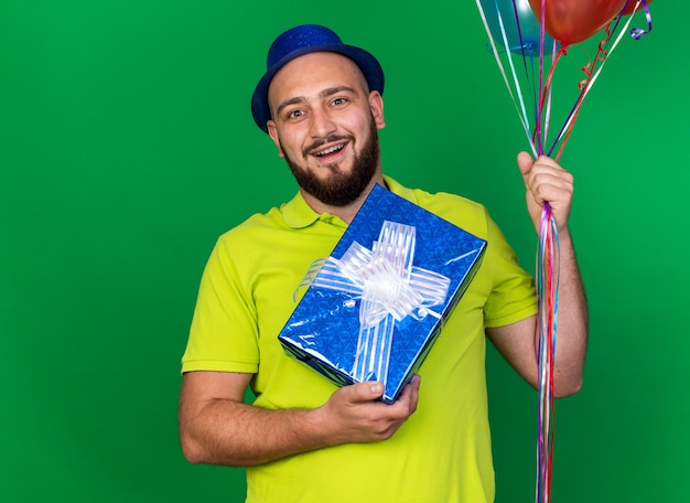 Zaskoczony młody człowiek ubrany w niebieski kapelusz imprezowy, trzymający balony z pudełkiem prezentowym