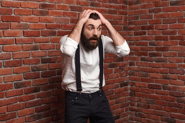 Zaskoczony, młody człowiek w garniturze z szelkami na mur z cegły.