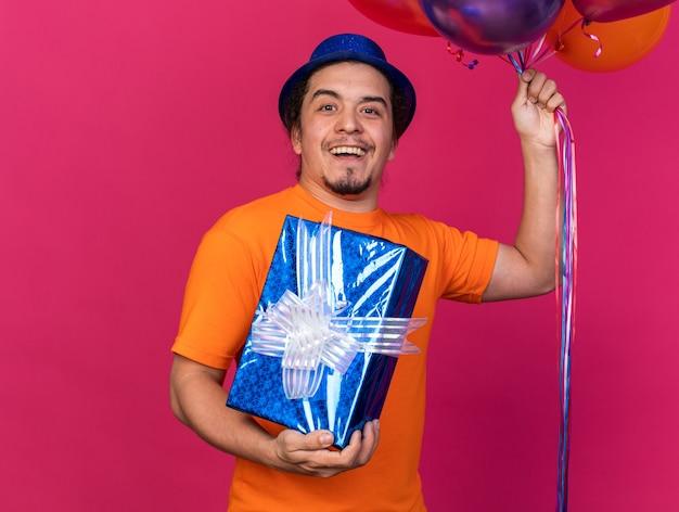 Zaskoczony młody człowiek w kapeluszu imprezowym, trzymający balony z pudełkiem na prezent na różowej ścianie