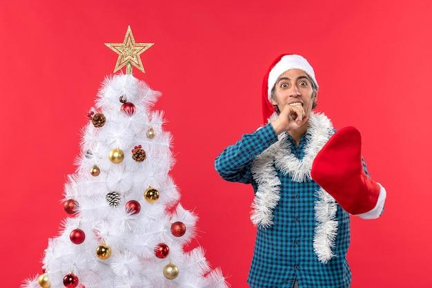 Zaskoczony młody człowiek w kapeluszu świętego mikołaja w niebieskiej koszuli w paski i na sobie swoją świąteczną skarpetę