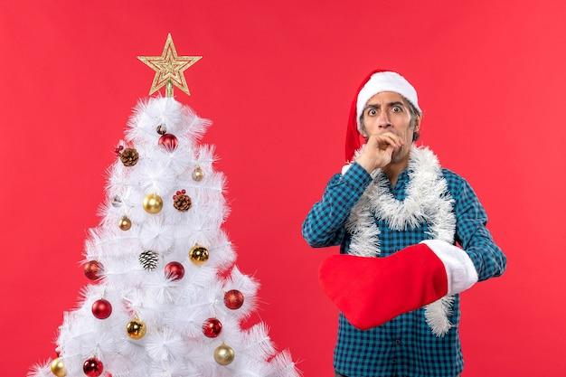 Zaskoczony młody człowiek w kapeluszu świętego mikołaja w niebieskiej koszuli w paski i pokazujący swoją świąteczną skarpetę