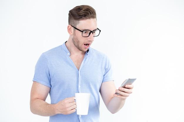 Zaskoczony młody człowiek w okularach przy użyciu smartfona