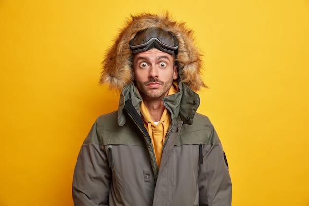 Zaskoczony młody człowiek w okularach snowboardowych wpatruje się w wytrzeszczone oczy oszołomione burzową zamiecią ubraną w zimową odzież wierzchnią.