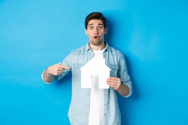 Zaskoczony, młody człowiek, wskazując na model karty domu i patrząc z przodu, stojąc przed niebieską ścianą