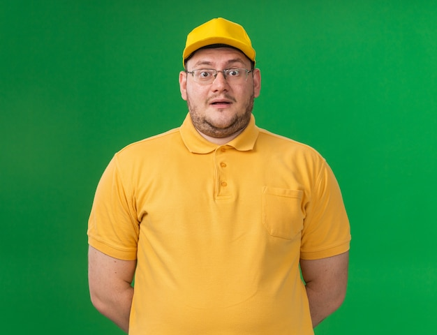Zaskoczony młody doręczyciel z nadwagą w okularach optycznych odizolowanych na zielonej ścianie z miejscem na kopię