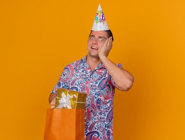 Zaskoczony, młody facet imprezowy w czapce urodzinowej, trzymając torbę na prezent i kładąc rękę na policzku na pomarańczowym tle