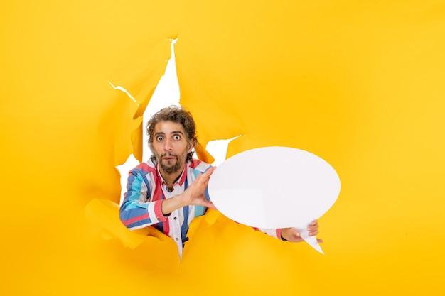 Zaskoczony młody facet wskazujący białą stronę z wolną przestrzenią w rozdartej dziurze w żółtym papierze