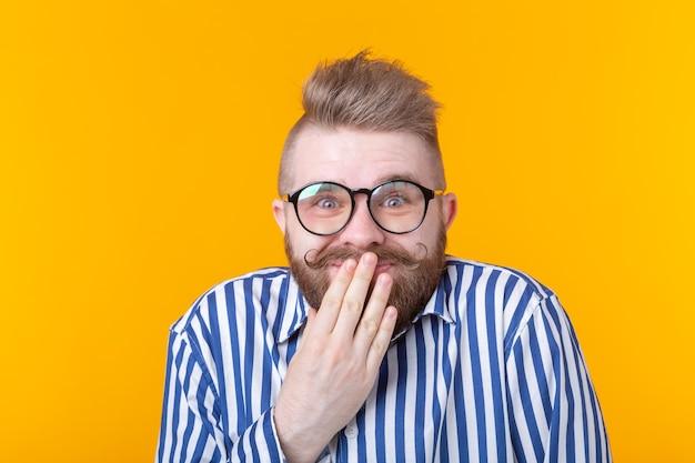 Zaskoczony młody hipster mężczyzna w okularach zawstydzony zakrywa usta i się śmieje