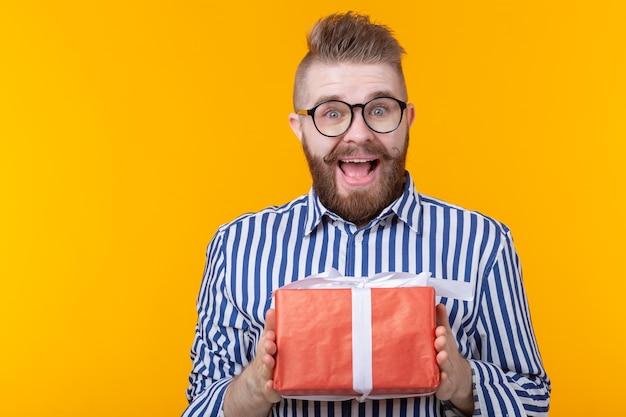 Zaskoczony młody hipster mężczyzna z wąsem i brodą ze zdziwienia rozpakowuje czerwone pudełko