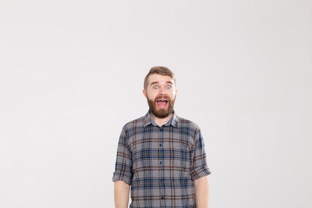 Zaskoczony młody hipster mężczyzna z wąsem, pozowanie na białym tle ze zdziwieniem, patrząc na