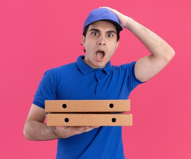 Zaskoczony młody kaukaski dostawca w niebieskim mundurze i czapce, trzymający paczki z pizzą, kładący rękę na głowie odizolowaną na różowej ścianie