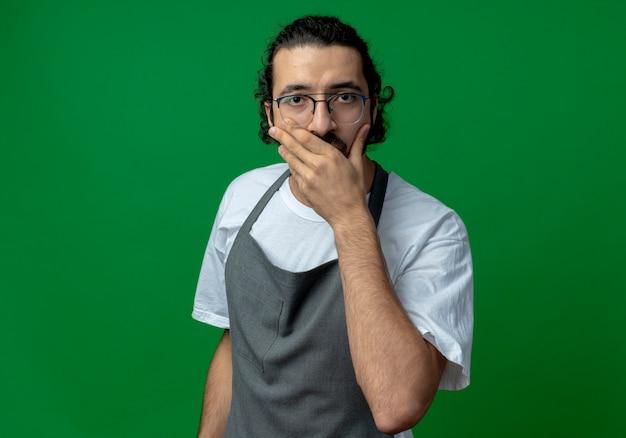 Zaskoczony młody kaukaski fryzjer męski na sobie mundur i okulary, kładąc rękę na ustach na białym tle na zielonym tle z miejsca na kopię