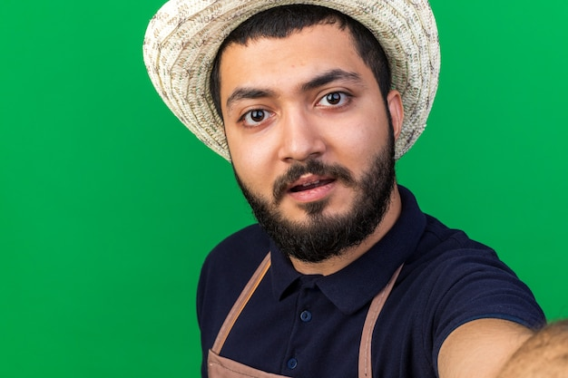 Zaskoczony młody kaukaski mężczyzna ogrodnik w kapeluszu ogrodniczym udaje, że robi selfie na zielonej ścianie z kopią miejsca