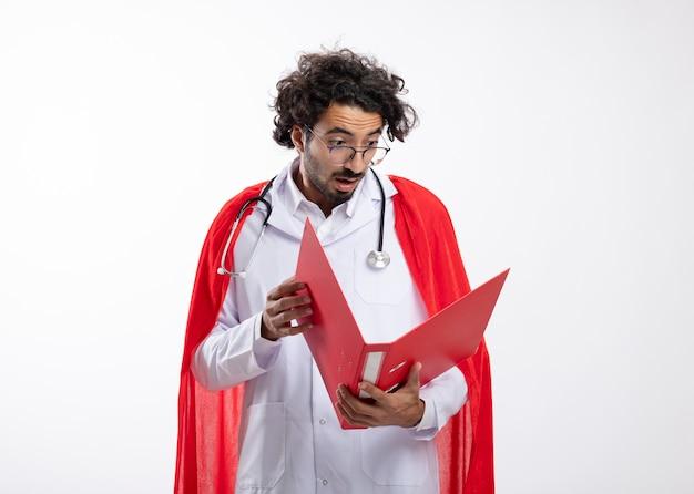 Zaskoczony młody kaukaski mężczyzna superbohatera w okularach optycznych w mundurze lekarza z czerwonym płaszczem i stetoskopem na szyi trzyma i patrzy na folder plików z miejscem na kopię