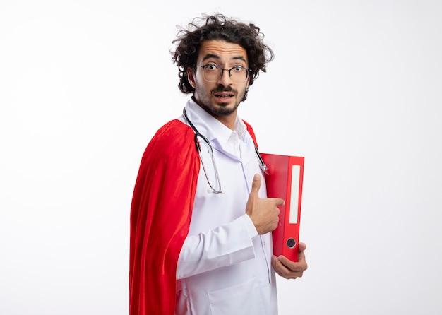 Zaskoczony młody kaukaski mężczyzna w okularach optycznych w mundurze lekarza z czerwonym płaszczem i stetoskopem na szyi stoi bokiem, trzymając i wskazując na folder plików z miejscem na kopię