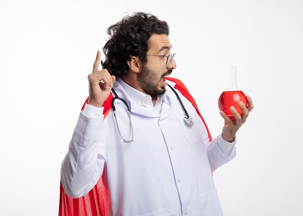Zaskoczony młody kaukaski mężczyzna w okularach optycznych w mundurze lekarza z czerwonym płaszczem i stetoskopem na szyi trzyma i patrzy na czerwony płyn chemiczny w szklanej kolbie skierowany w górę