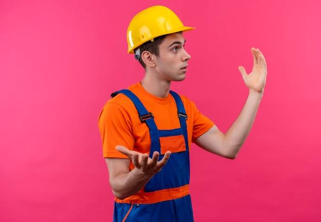 Zaskoczony młody konstruktor w mundurze konstrukcyjnym i kasku ochronnym